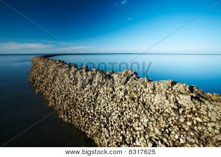 Seawall under deep blue sky