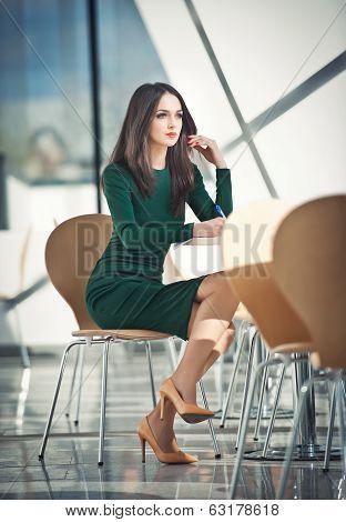Fashion attractive girl in dark green dress sitting on chair writing, indoor shot. Modern urban