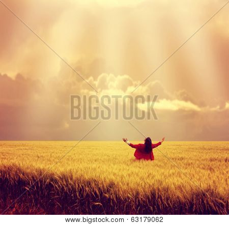 man in wheat field during sunset done with a warm autumn filter