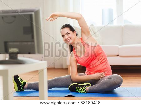 fitness, home and diet concept - smiling teenage girl streching on floor and watching tv at home