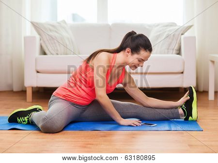 fitness, home, technology and diet concept - smiling teenage girl streching on floor with smartphone at home