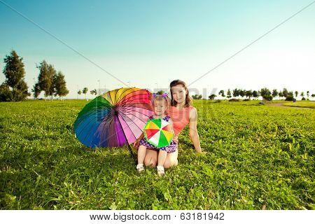 Beautiful little girl with mother rainbow umbrella holding  in  the park. Smiling child and mom on a field with flowers. Kid with mum rest on the  nature. Family outdoor