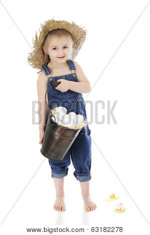 An adorable, preschool farm girl whose dropped eggs from her pail while happily showing them off -- oblivious.  On a white background.