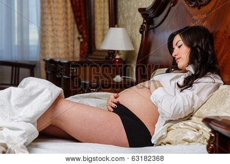 Pregnant Woman Lies On Bed.