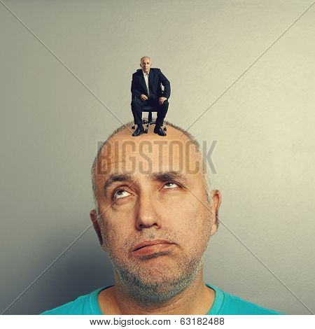 weary senior man with small businessman on his head