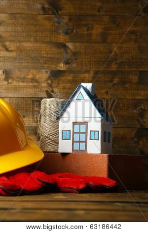 Composition with safety helmet, leather gloves, tools and decorative house on wooden background