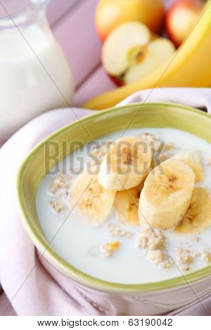 Tasty oatmeal with bananas and milk on table close up