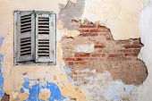 stock photo of jalousie  - Grunge damaged brick wall with closed window - JPG