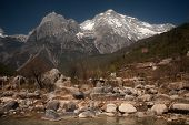 stock photo of jade blue  - White Water River Waterfall Under The Mountain Range With Nobody In Lijiang Near Jade Dragon Snow Mountain in Yunnan province,Southwestern of China.
