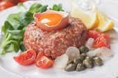 Tartar steak, raw meat steak with capers, onion and cherry tomato