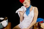 stock photo of flight attendant  - Retro Airline Stewardess or Flight Attendant Removing Her Shirt After Work - JPG