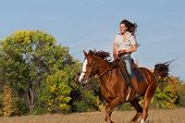 image of horse girl  - Beautiful girl  riding a horse on autumn field - JPG
