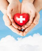 family health, charity and medicine concept - male and female hands holding red heart with cross sig