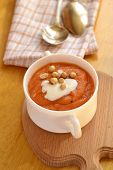 Carrot soup with sour cream and peanuts