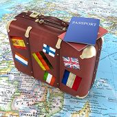picture of old suitcase  - old suitcase with passports and striples flags on world map background - JPG