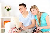 Couple playing video games on home interior background