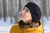 stock photo of beret  - Portrait of a woman in a black beret and a yellow jacket on a background of forest - JPG