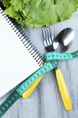 Cutlery tied with measuring tape and notebook with lettuce on wooden background
