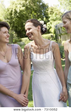 Bride With Two Women In Garden, Holding Hands, Smiling, Portrait