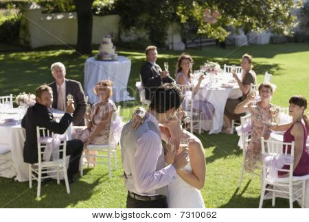 Mid Adult Bride And Groom In Garden Among Wedding Guests, Holding Wineglasses, Kissing
