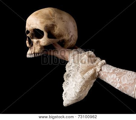 Creepy human skull held by a female hand wearing antique lace sleeves