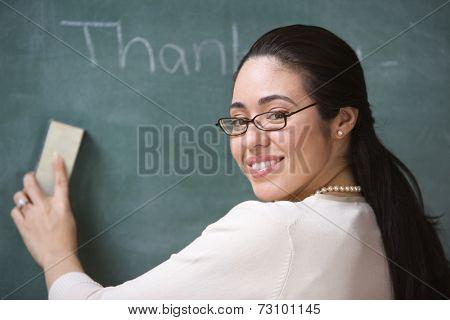 Portrait of female teacher erasing chalkboard