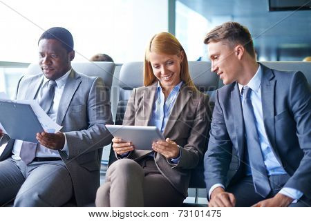 Young businesswoman with touchpad and her two colleagues working with data in airport