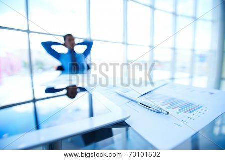 Business documents, touchpad and pen at workplace on background of male employee