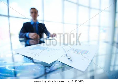 Close-up of business documents and pen at workplace on background of office worker