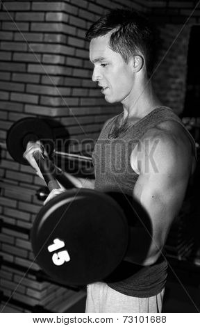 Young sporty man training in gym with barbell