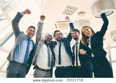 Group of ecstatic business leaders with raised arms expressing their gladness