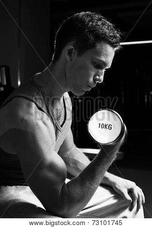 Black-and-white image of handsome man training in gym with dumbbell