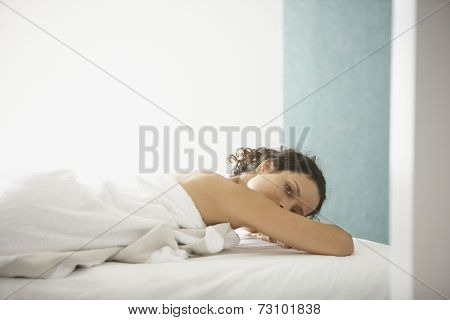 Portrait of woman wrapped in towel laying on bed