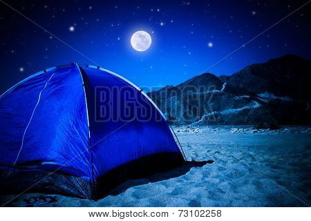 Camp tent on the beach at night, full moon glowing in dark night, summer adventure and active lifestyle concept