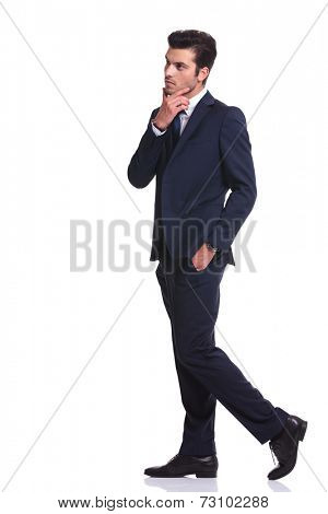 Business man walking with one hand in his pocket and the other one to his chin, thinking of somethind important