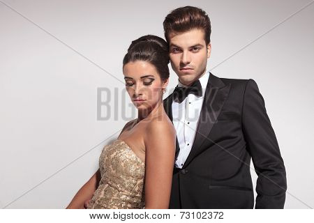Close up of an elegant couple posing on grey studio background, the woman is leaning on her lover looking down, while he is looking at the camera.
