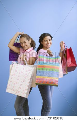 Portrait of two teenage girls holding gift bags