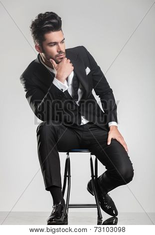 Elegant young man in tuxedo sitting on a stool, looking away from the camera, thinking and holding one hand to his chin.