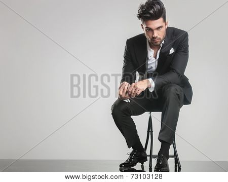 Elegant young man in tuxedo sitting on a stool while holding his finger, looking at the camera.