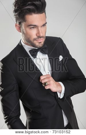 Angle view of an elegant young man ajusting his tuxedo, looking away from the camera.