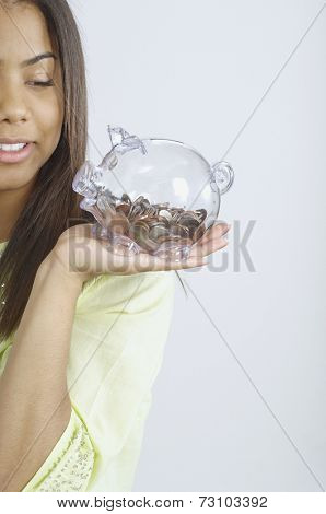 Teenage girl holding a glass piggy bank