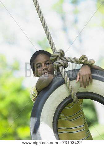 Portrait of boy on tire swing
