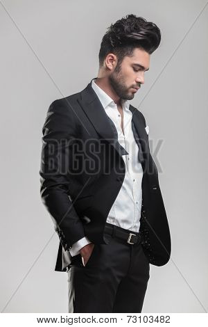 Portrait of an elegant young man in tuxedo holding his hands in pocket while looking down