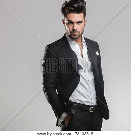 Picture of an elegant young man in tuxedo looking at the camera while holding his hands in pocket. On grey background