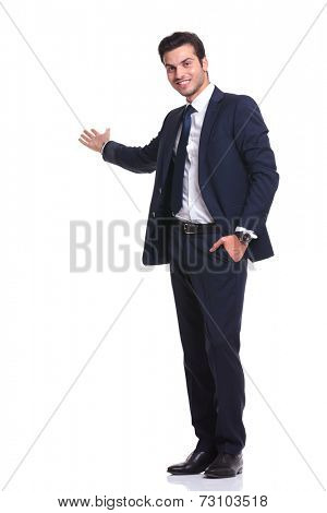 Side view of a happy business man welcoming you with one hand in his pocket while smiling, on white background