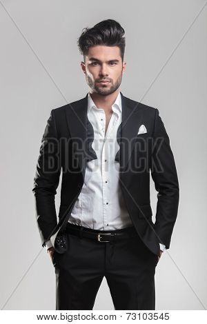 Fashion young man in tuxedo looking at the camera while holding his hands in pocket. On grey background.