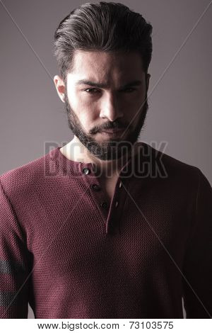 Closeup of a handsome beard man in burgundy sweater, looking at the camera, on grey background