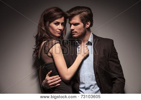 Close up picture of a couple embracing, the woman is looking into the camera while the man is looking away. On dark grey background.