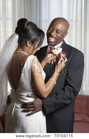 Bride pinning flowers onto groom's lapel