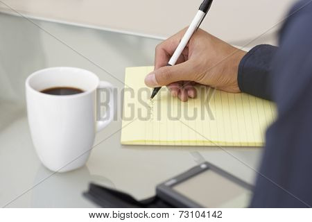Businesswoman writing on a yellow pad